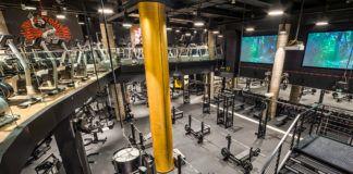 Wnętrze dwupoziomej siłowni z żółtą kolumną po środku