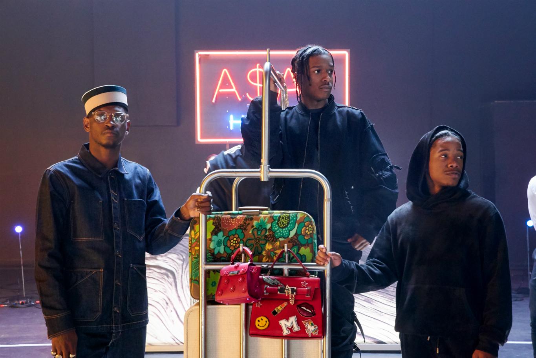 Trójka czarnoskórych mężczyzn trzymająca hotelowy wózek z kolorowymi bagażami