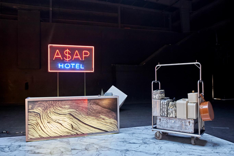 Widok na wnętrze z kontuarem, hotelowym wózkiem bagażowym i neonem z napisem ASAP ROCKY