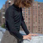 Mężczyzna z włosami do ramion w szarych spodniach i czarnej koszuli w jaśniejsze paski stoi i patrzy na miasto, nie widać twarzy