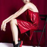 Kobieta siedząca na krześle w czerwonej sukience, na czerwonym tle w czarno-czerwonych butach