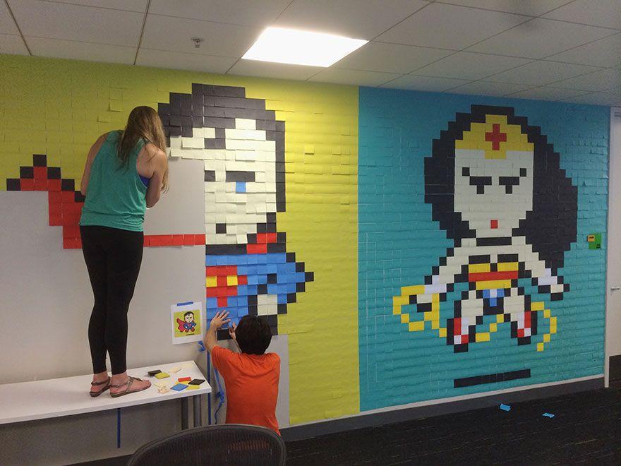 Pracownicy biura przyklejący do ścian samoprzylepne karteczki, które tworzą obrazek supermana