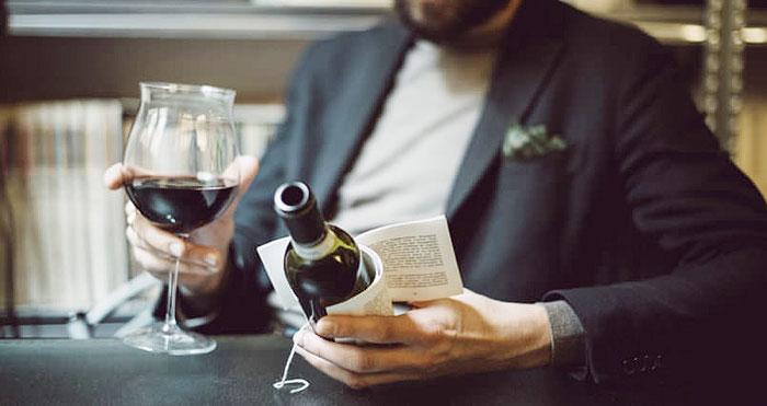 Mężczyzna trzymający kieliszek wina i butelkę z książką