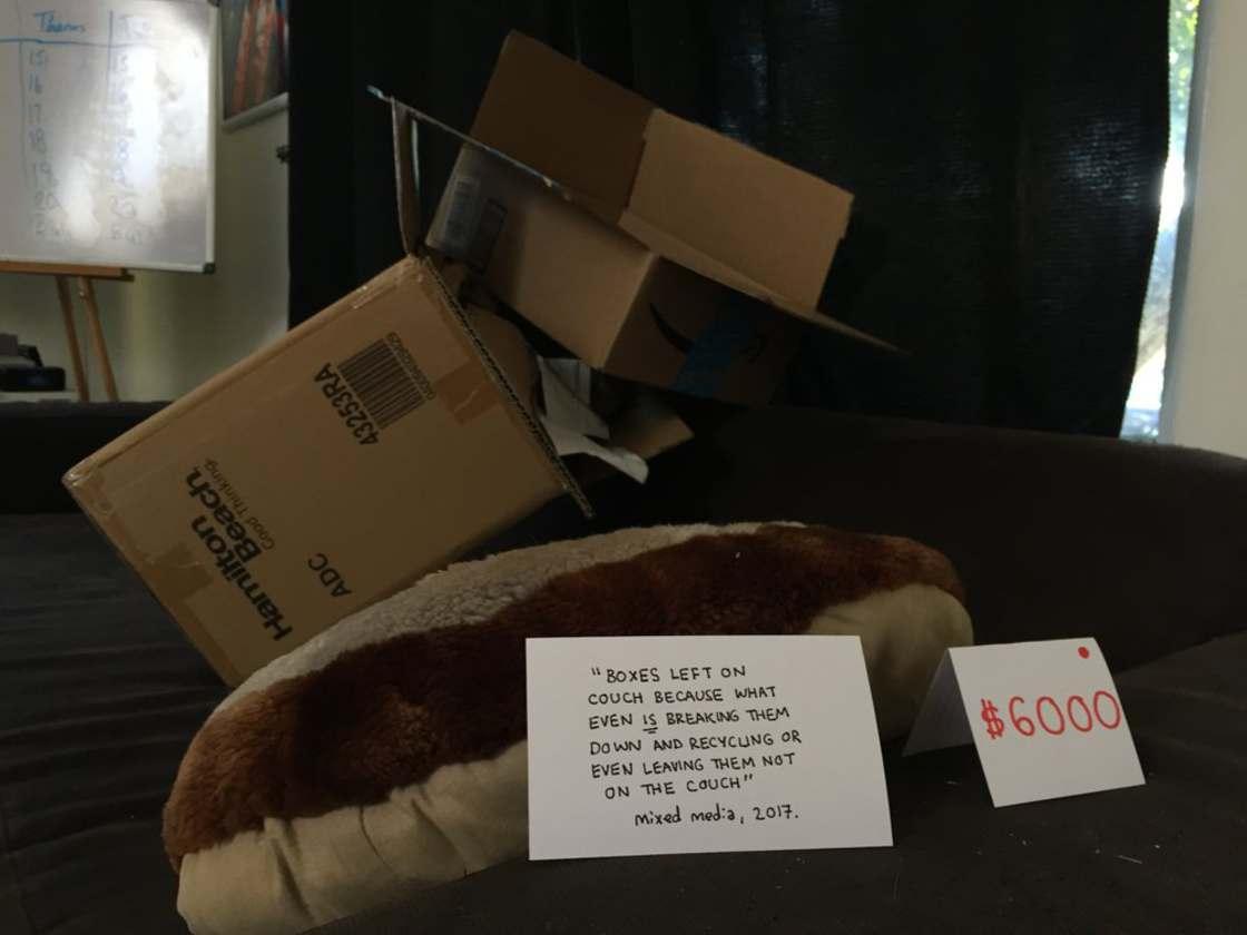 Zdjęcie przedstawia stertę kartonów i karteczkę z opisem i ceną