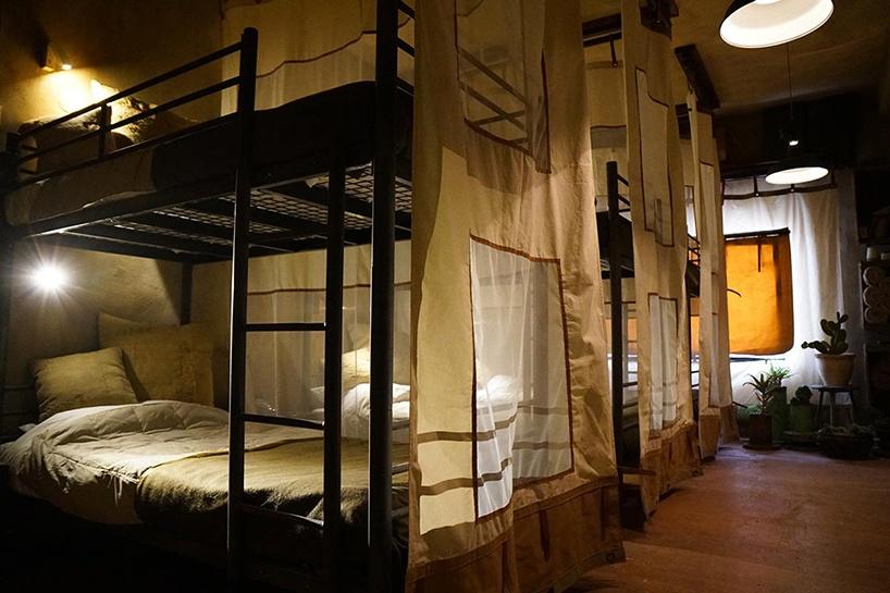 Sypialnia przypominajaca wojskowe lozka w hotelu banksyego