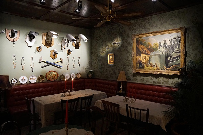 Widok pokoju ze stołami, krzesłami i wiszącymi obrazami