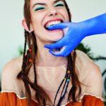 Dziewczyna w warkoczykach na głowie gryząca palec polamowanej na niebiesko dłoni