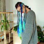 Dziewczyna w swetrze i kolorowych warkoczykach na głowie