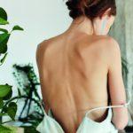 Dziewczyna stojąca tyłem w sukience z odkrytymi plecami