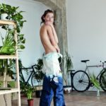 Dziewczyna stojąca w jeansownych stpodniach, bez bluzki, zakrywająca piersi rękami
