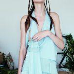 Dziewczyna w warkoczykach na głowie i miętowej sukience