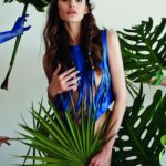 Dziewczyna w niebieskiej bluzce z pasków, zakrywająca dolne partie ciała rośliną