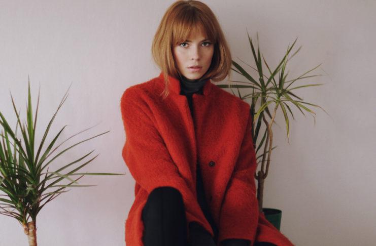Rudowłosa dziewczyna z grzywką w czerwonym płaszczu siedzaca na szafce