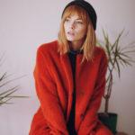 Dziewczyna z grzywką, w czarnej czapce, czerwonym płaszczu i ciemnych spodniach, siedząca na szafce, w tle roślina doniczkowa