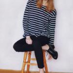 Dziewczyna z grzywką w czerwonej czapce, bluzce w paski i ciemnych spodniach, siedzaca na stołku