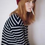 Dziewczyna z grzywką w czerwonej czapce i bluzce w paski siedząca profilem z papierosem w ustach