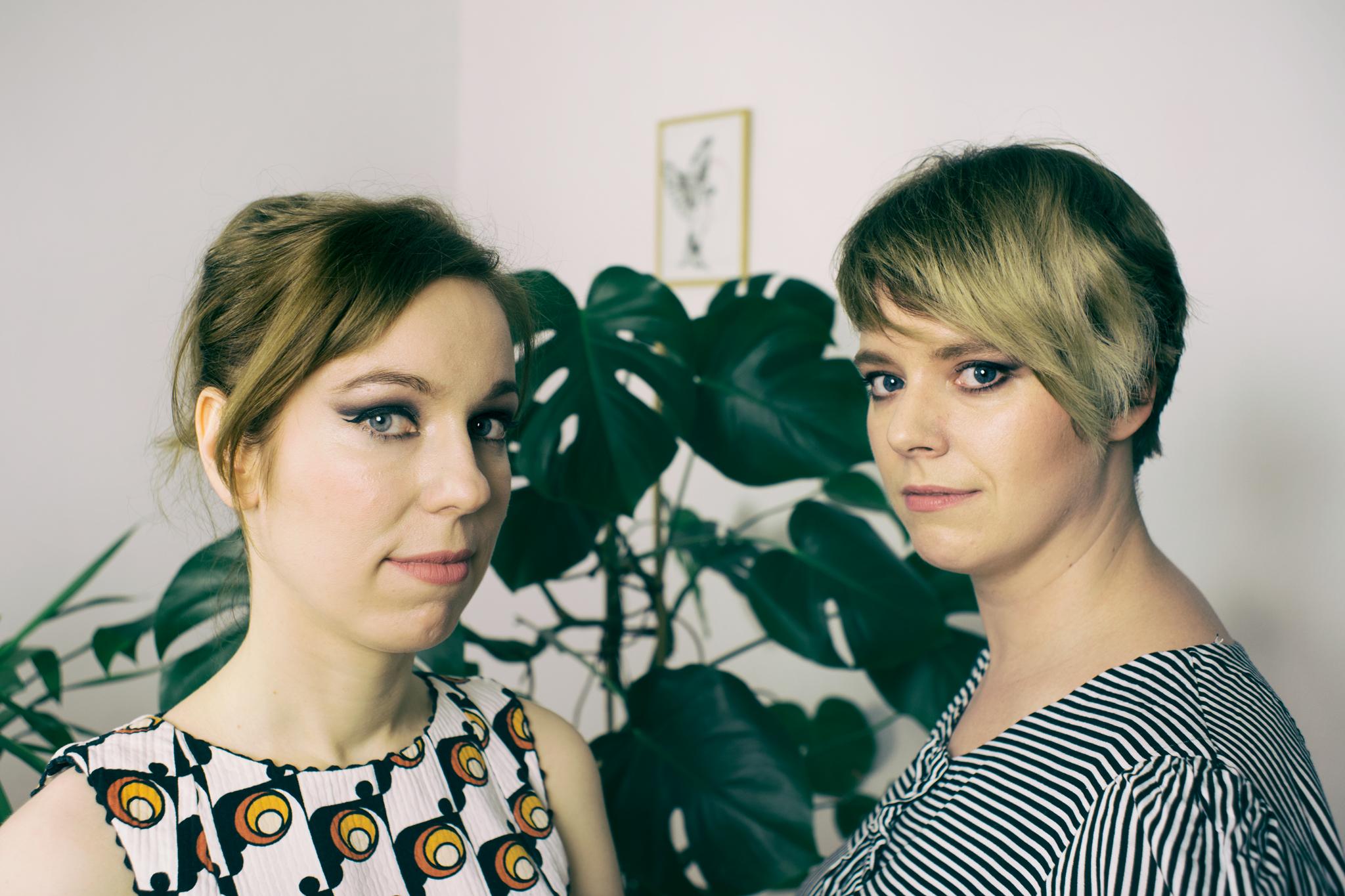 Dwie dziewczyny na tle roślin i białej ściany