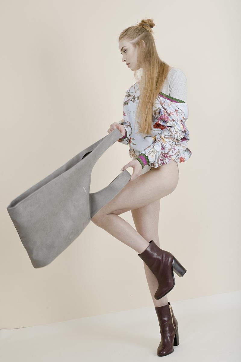 Skacząca dziewczyna w brązowych botkach, kwiecistej bluzce, bez spodni, z szarą torbą w ręku