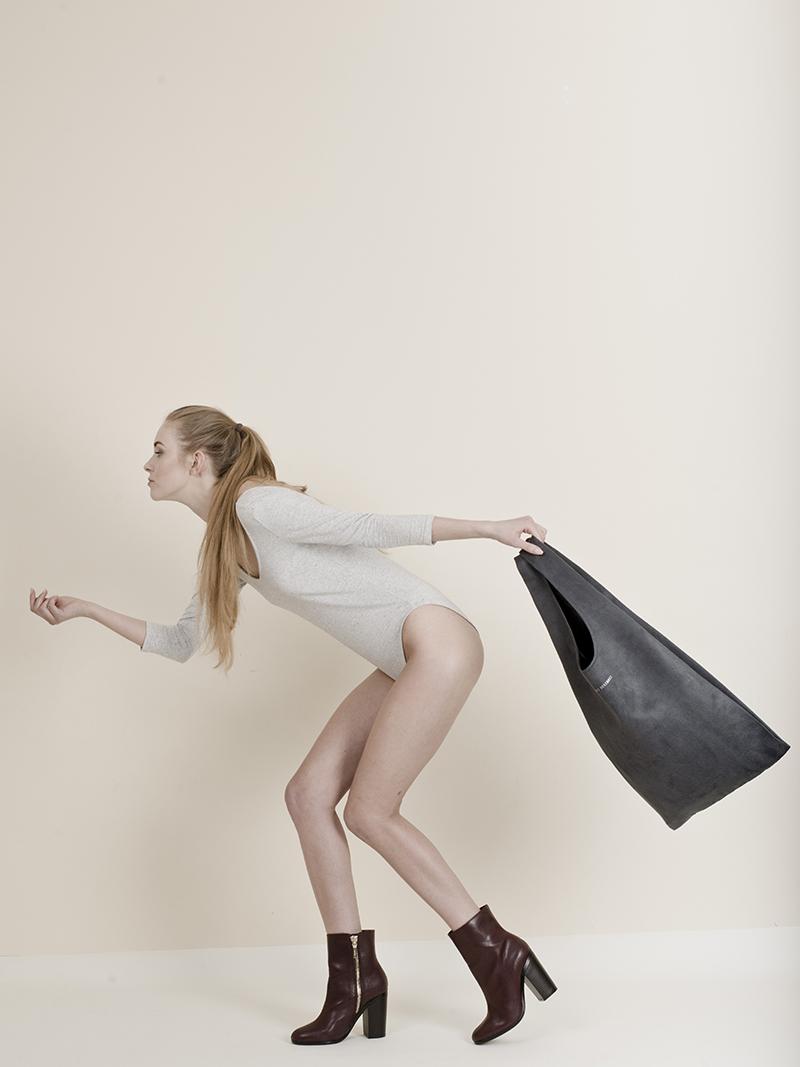 Dziewczyna w kucyku na głowie i jasnym body, bez spodni, wychyla się trzymając torbę z tyłu