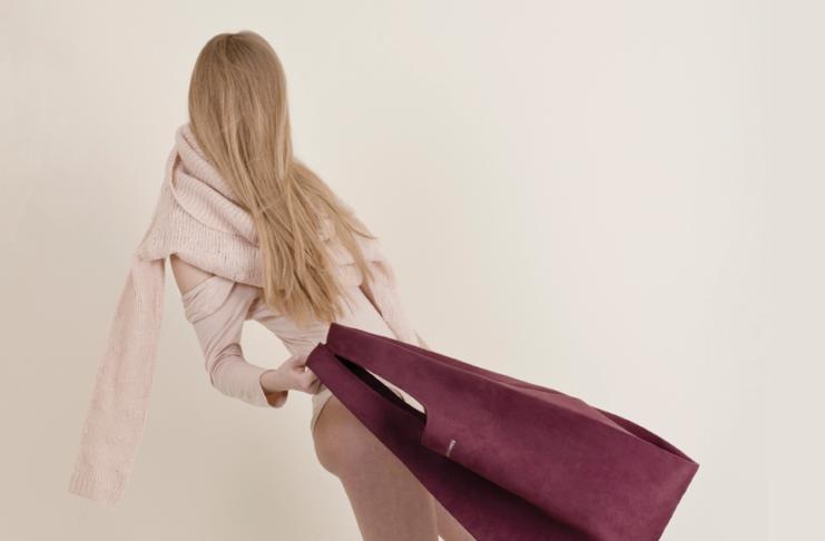 Dziewczyna w różowym narzuconym na ramiona swetrze, machająca bordową torbą
