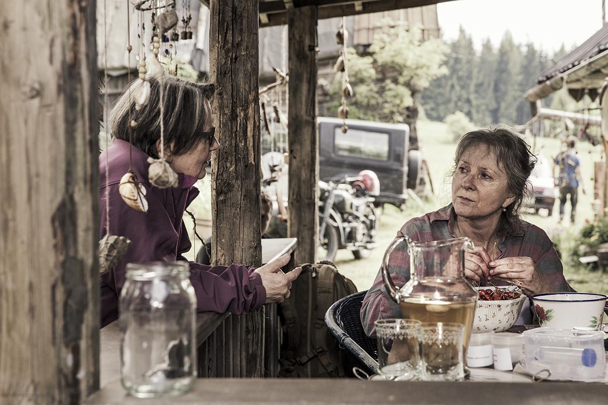 Kobieta siedząca w altanie przed domem i druga opierająca się o balustradę