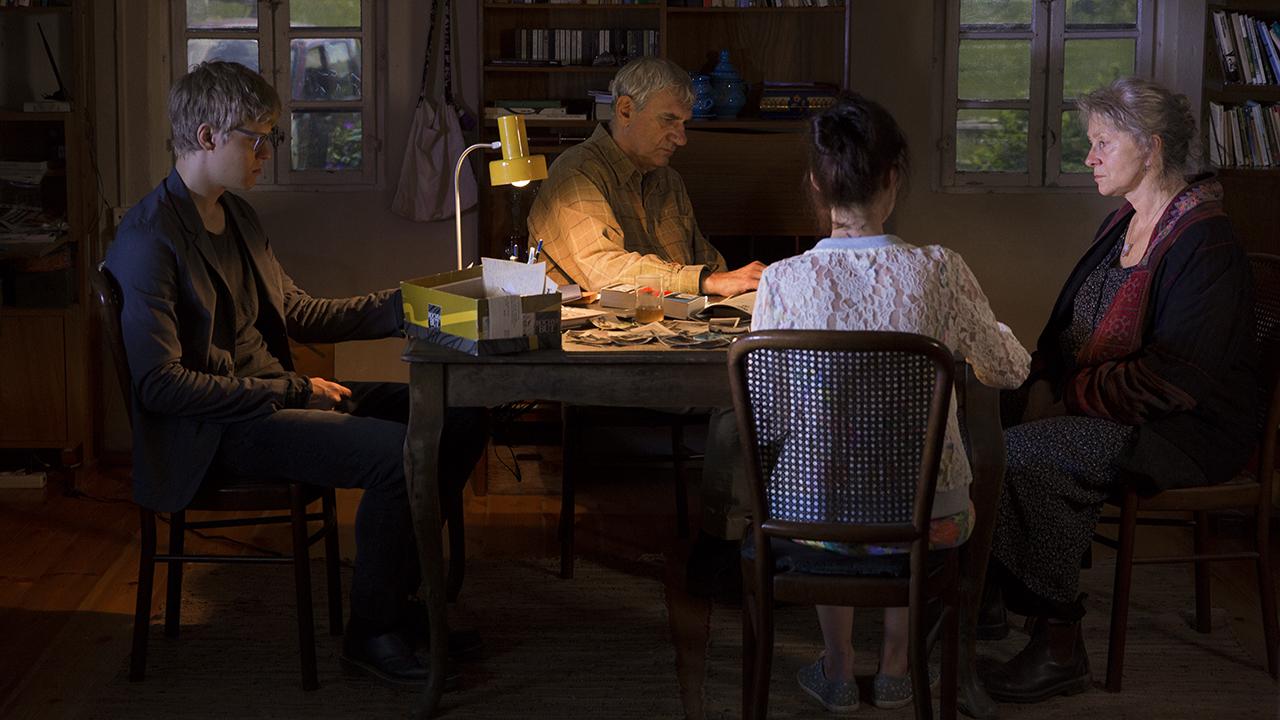 W ciemnym pokoju przy biurku siedzi mężczyzna, a naprzeciwko niego kobieta