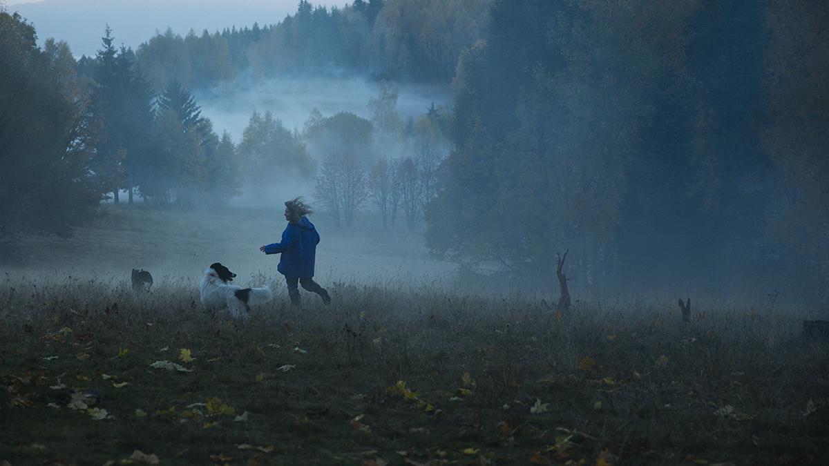 Widok lasu z mgłą, biegnącej dziewczyny i dwóch psów
