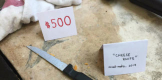 Zdjęcie przedstawia widok brudnego noża na blacie oraz karteczki z jego ceną