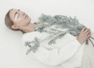 Dziewczyna ubrana w biały płaszcz, leży na białej podłodze, w rękach trzyma gałązki