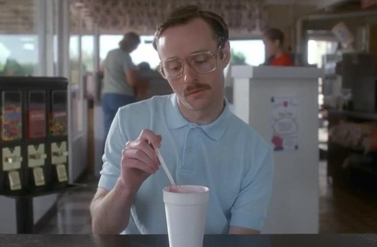 Mężczyzna w niebieskiej koszulce, trzymajacy za słomkę w napoju