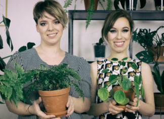 Dwie uśmiechnięte dziewczyny trzymające w dłoniach doniczki z kwiatami