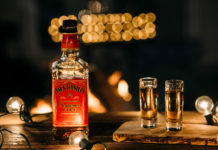 Butelka Jack Daniel's obok niej dwa kieliszki, w tle widać delikatne światła