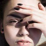 Portret dziewczyny trzymającej rękę na twarzy z kolczykiem w dolnej wardze