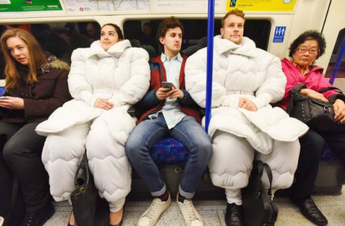 Dwoje ludzi, kobieta i mężczyzna siedzacy w metrze ubrani w strój, który wygląda jak kołdra
