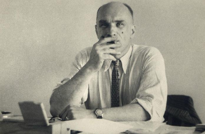 Mężczyzna siedzący przy biurku, palący papierosa
