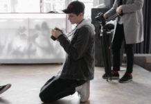 Mężczyzna z aparatem, klęczący na podłodze