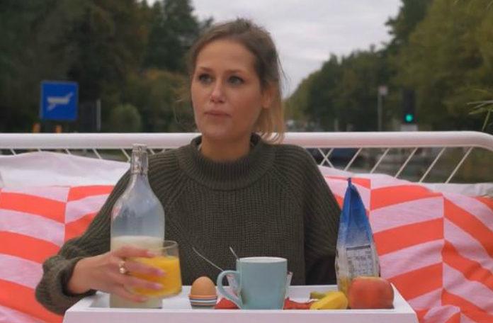 kobieta płynąca łodzią, znajduje się w lóżku, nad którym stoi stolik z jedzeniem i kawą