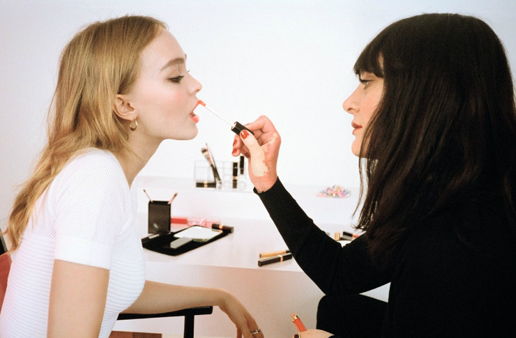 Na zdjeciu sa dwie kobiety blondynka i brunetka na tle stolu plenego kosmetykow. Brunetka maluje usta blondynce