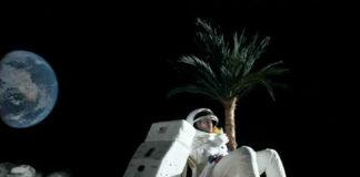 Mężczyzna na księżycu, siedzi na leżaku, obok palma