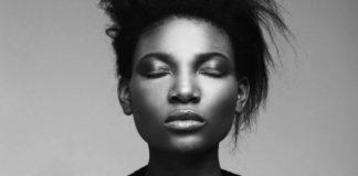 """Czarnoskróra dziewczyna z zamkniętymi oczami, trzymająca napis """"ojczyzna"""""""