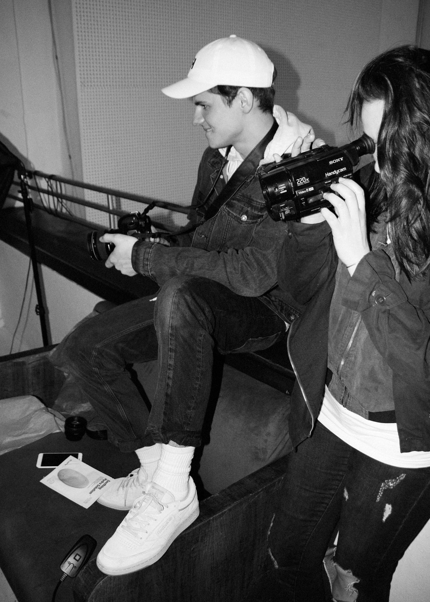 Czarnobiałe zdjęcie mężczyzny siedzącego na podłodze i kobiety trzymającej kamerę