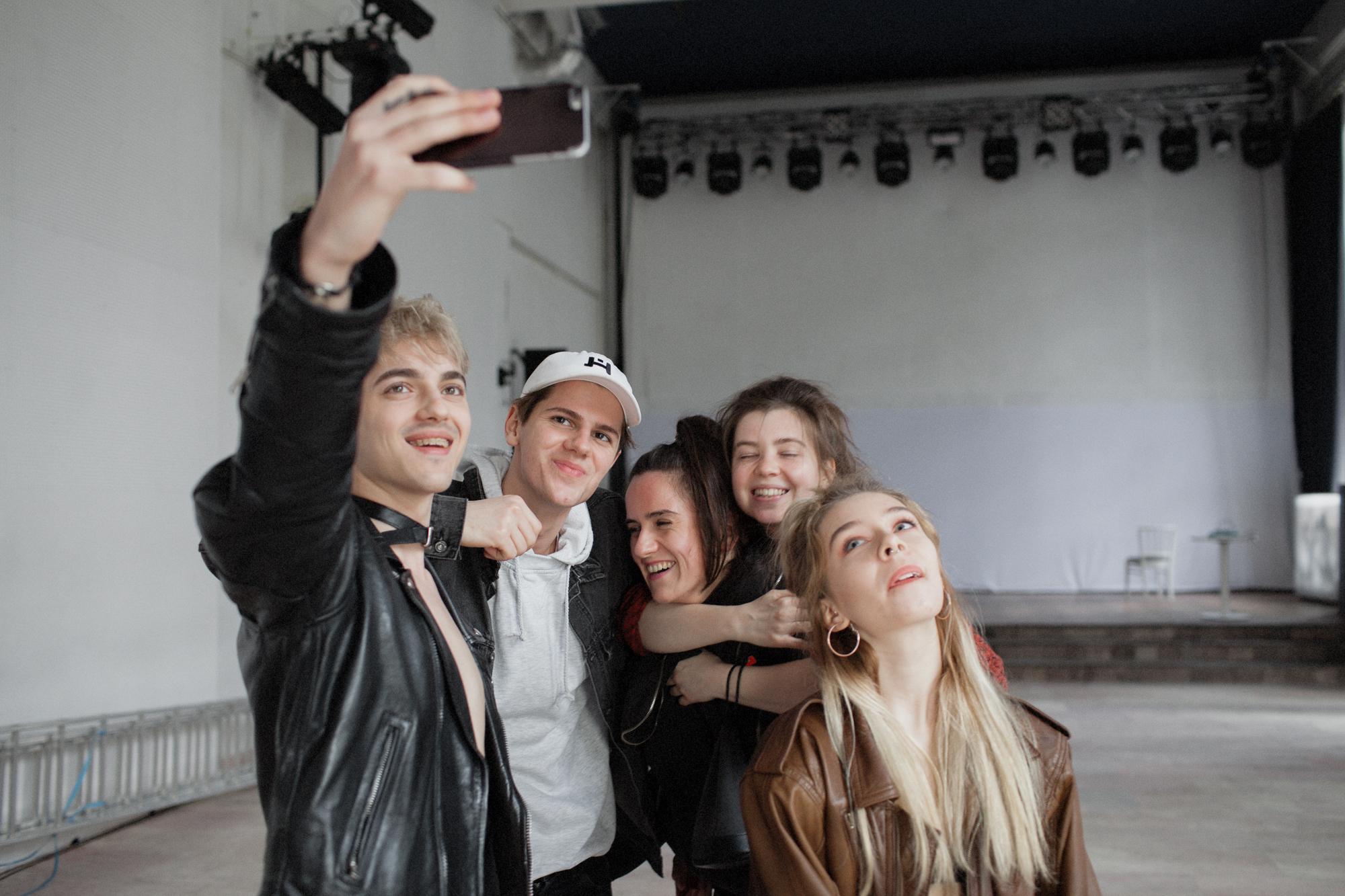 Dwóch chłopaków i trzy dziewczyny robią sobie selfie smartfonem