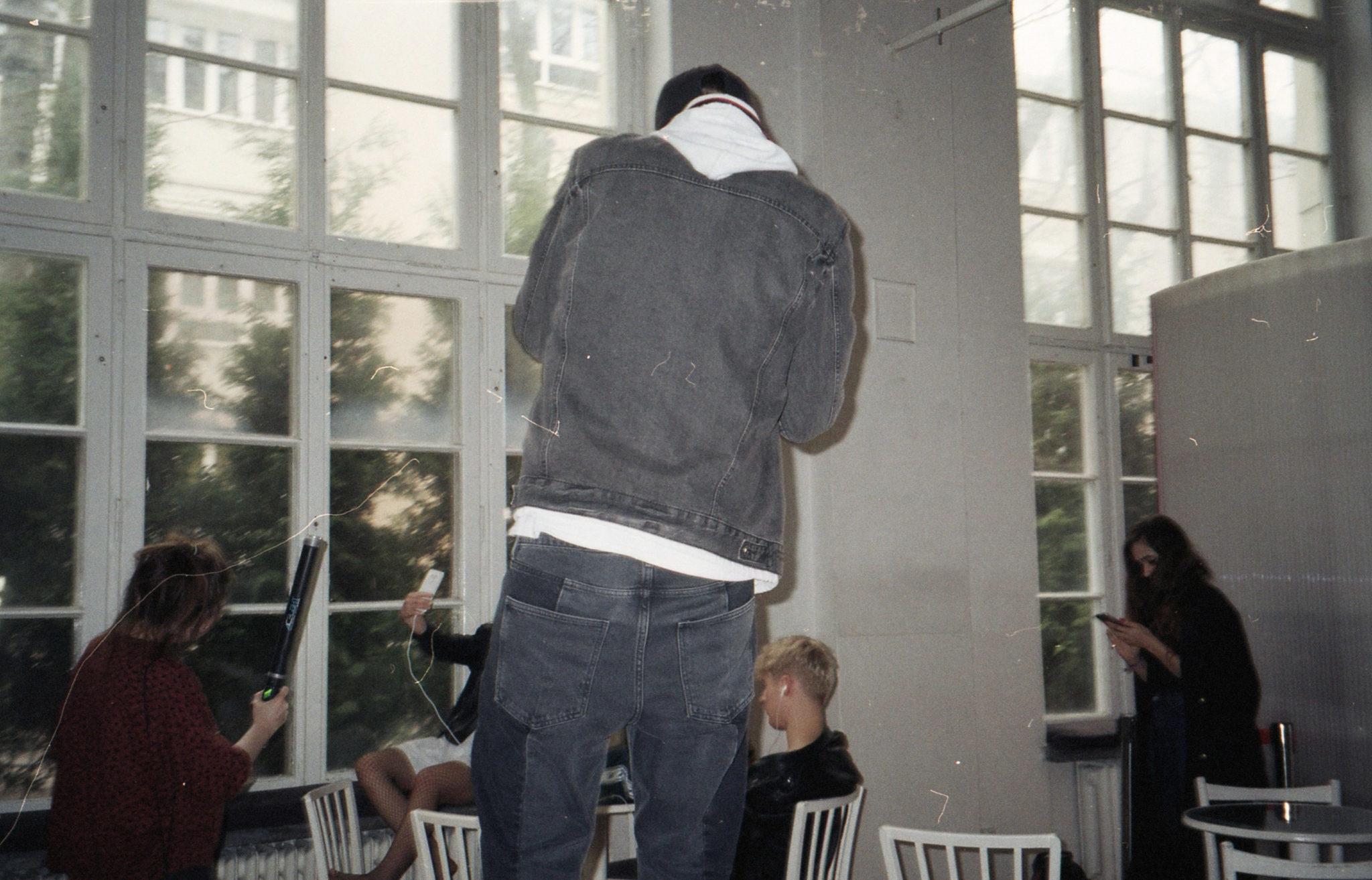 Mężczyzna stojący tyłem, ubrany w kurtkę, bluzę z kapturem i ciemne spodnie