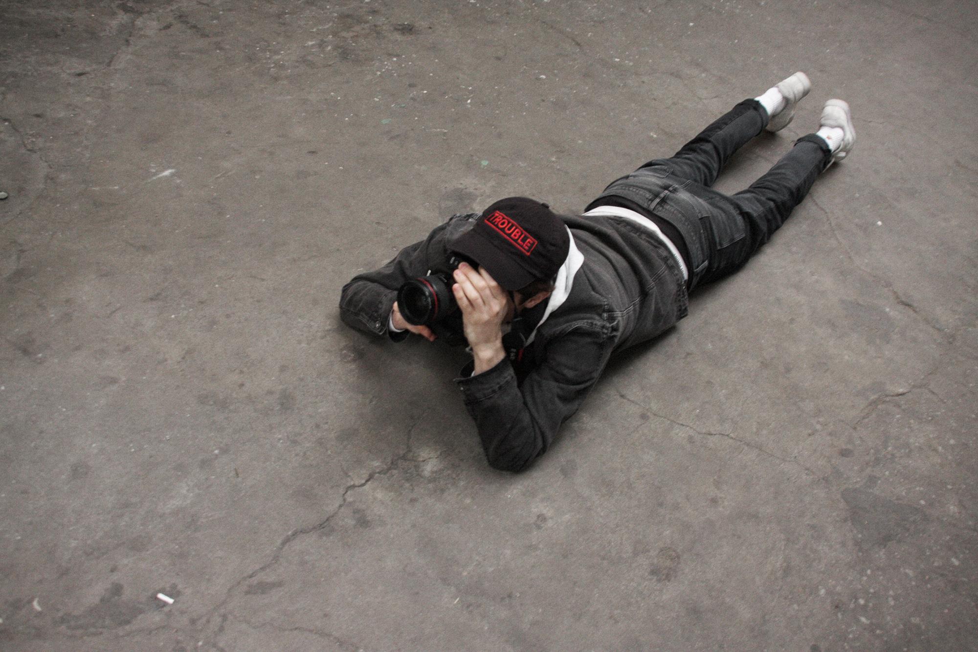 Mężczyzna z aparatem, leżący na ziemi