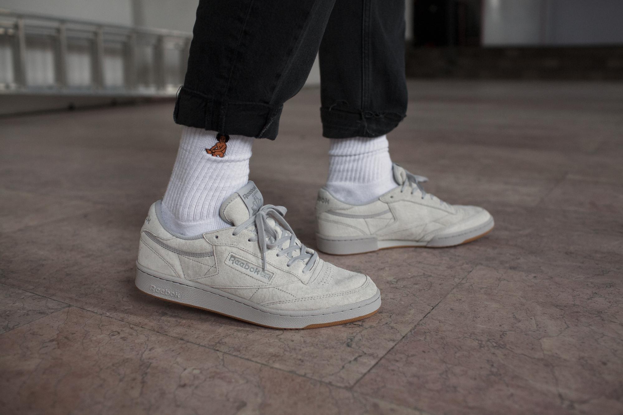 Białe buty Reebok Classic na nogach mężczyzny, białe skarpetki, czarne spodnie