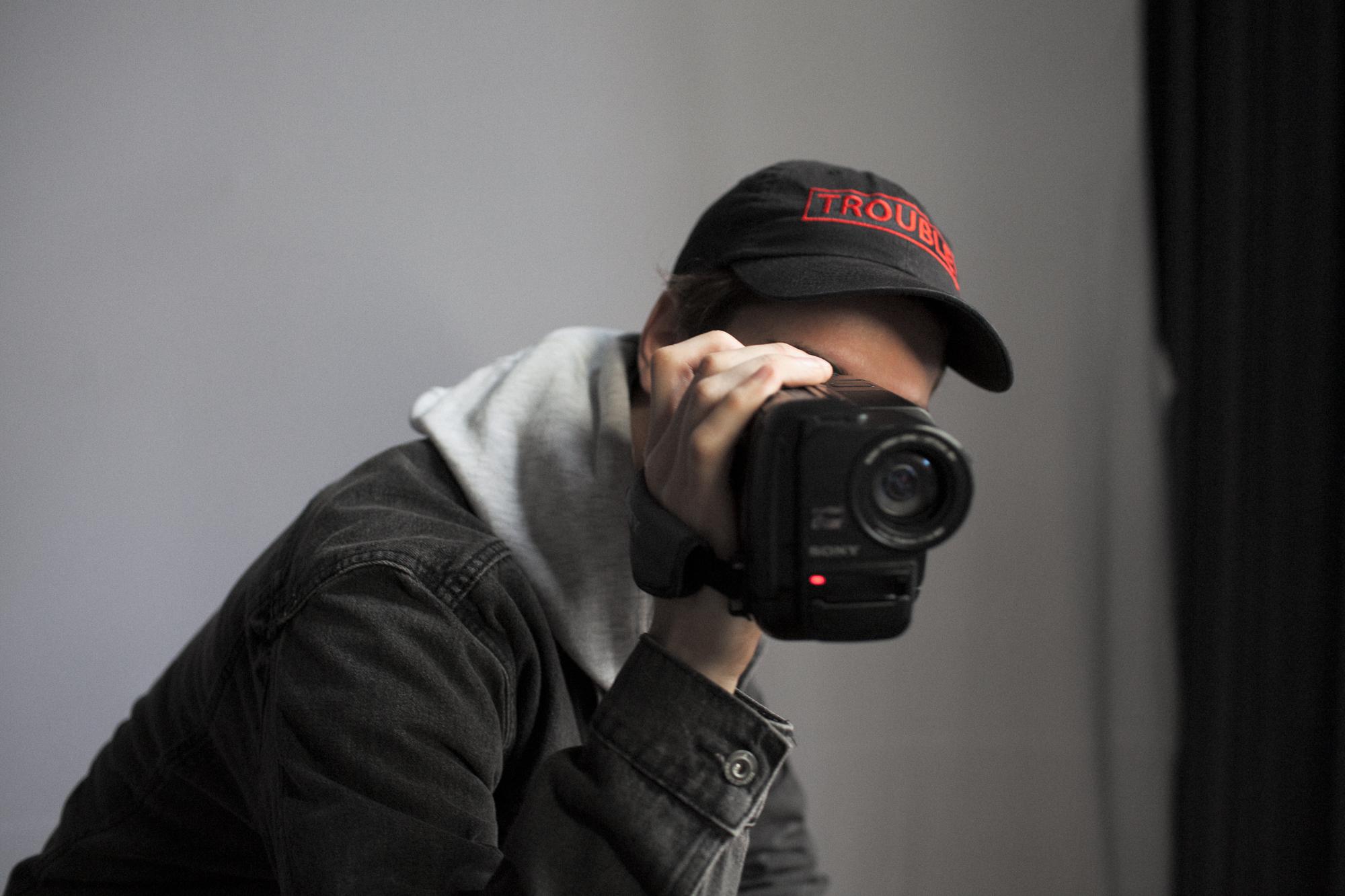 Mężczyzna w kurtce i bluzie z kapturem, na głowie czapka z daszkiem, trzymający na wysokości twarzy kamerę