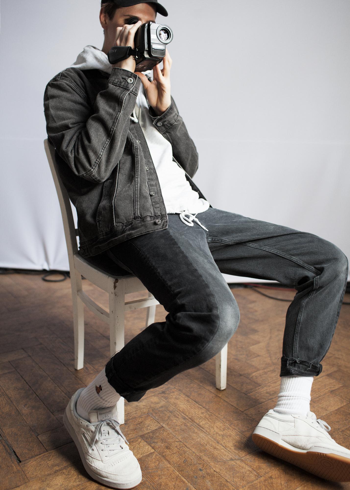 Mężczyzna siedzący na krześle, z kamerą w ręku, ma na sobie kurkę, bluzę, ciemne spodnie i jasne buty Reeboka