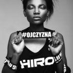 """Czarnoskróra dziewczyna z zamkniętymi oczami, trzymająca napis """"ojczyzna"""" w koszulce HIRO"""