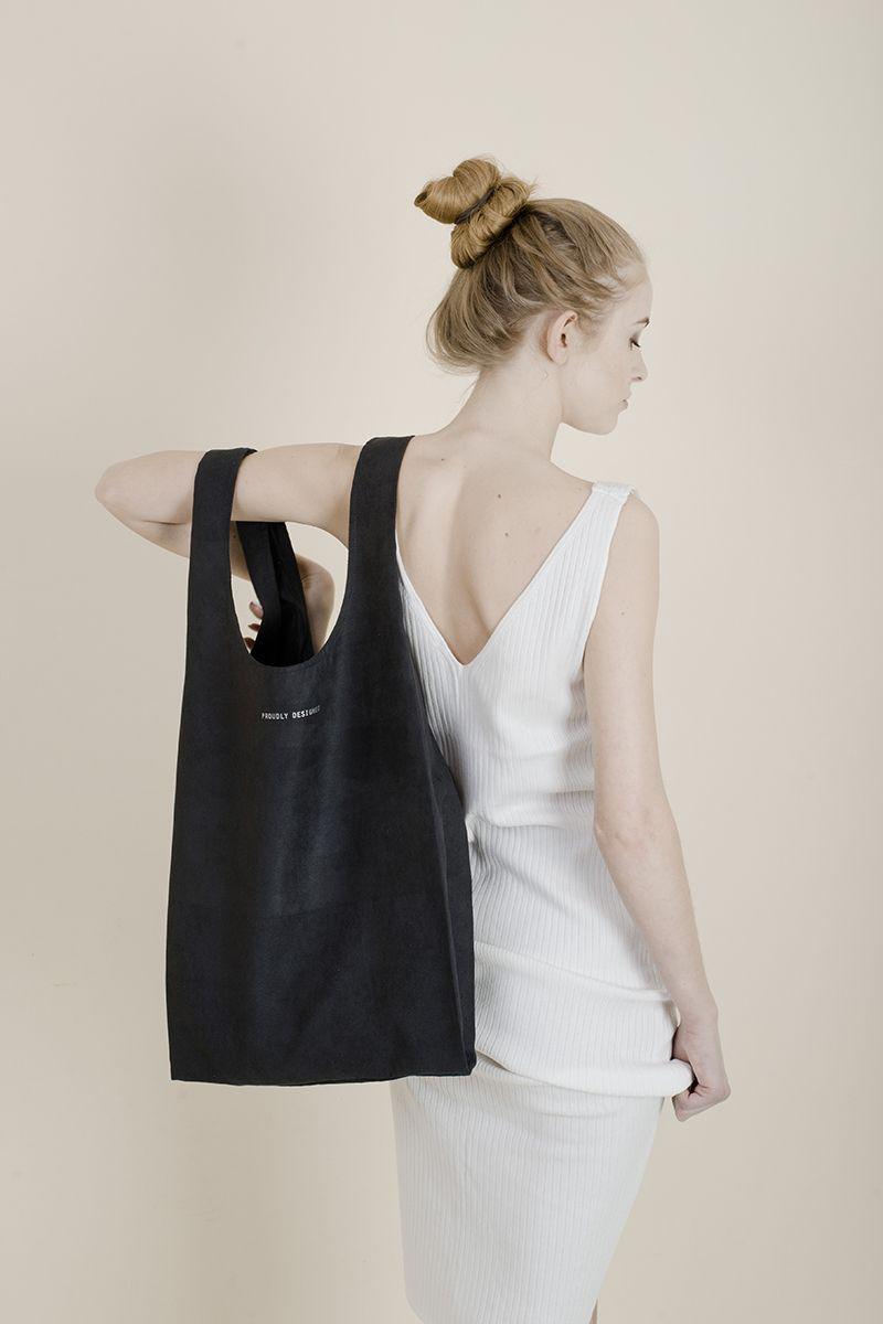 Dziewczyna w jasnej sukience z odkrytymi plecami i ciemną torbą na ramieniu