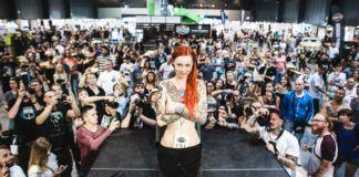 Dziewczyna w tatuażach stojąca na scenie, dookoła ludzie